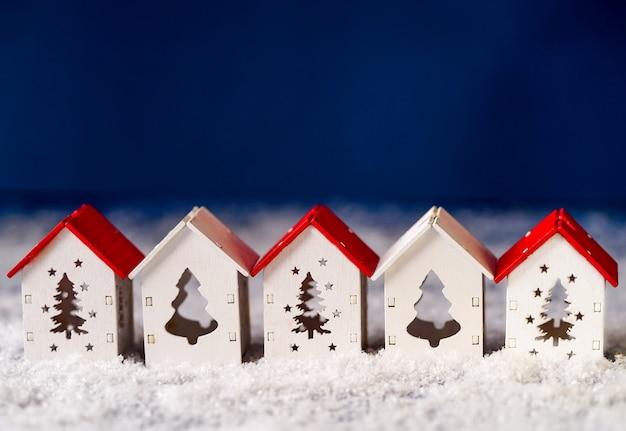 Witte huisjes met rode en witte daken op een blauwe achtergrond met sneeuw, een wenskaart voor een gelukkig nieuwjaar en kerstmis.