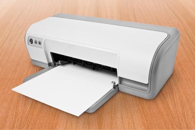 Witte inkjetprinter met papier boven tafel