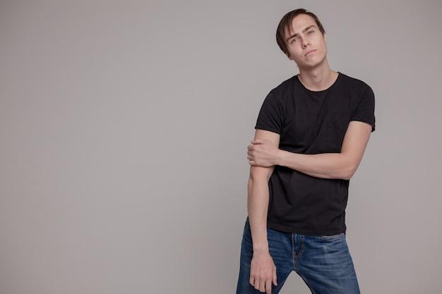 Witte jonge man in een zwart t-shirt en spijkerbroek. emotie.
