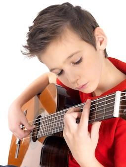 Witte jongen speelt op akoestische gitaar op wit wordt geïsoleerd