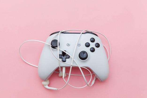 Witte joystick en oortelefoons op roze achtergrond.