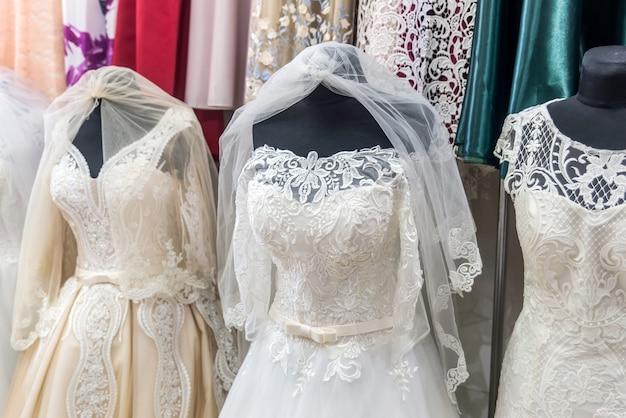 Witte jurken op mannequins in huwelijkssalon