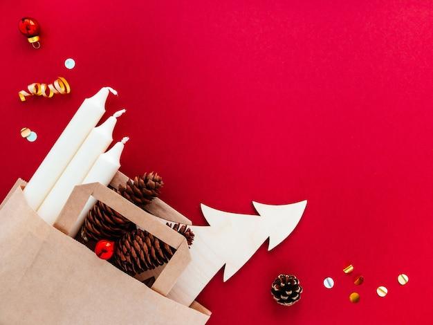 Witte kaarsen, kegels, kerstboom in een handwerkzak