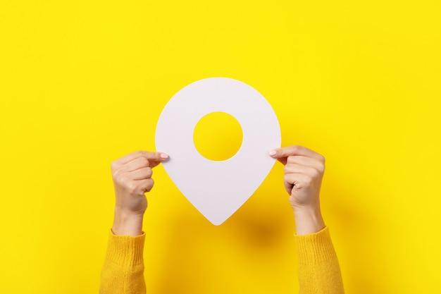 Witte kaart aanwijzer 3d pin in hand over gele achtergrond