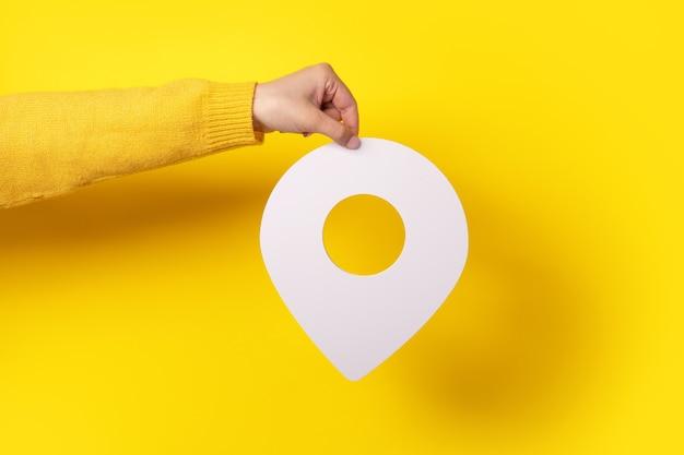 Witte kaart aanwijzer 3d-pin. locatie symbool in de hand op gele achtergrond
