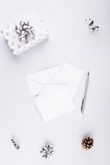 Witte kaart en enveloppen voor cadeau in zilveren verpakking. concept voorbereiding op vakantie