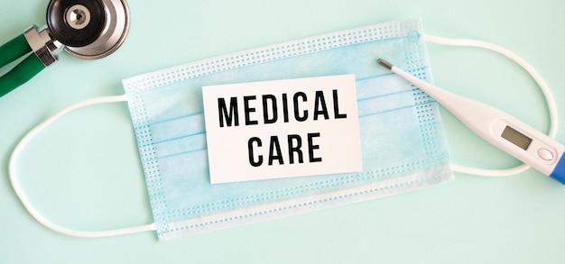 Witte kaart met de inscriptie medische zorg op een medisch beschermend masker. medisch concept.