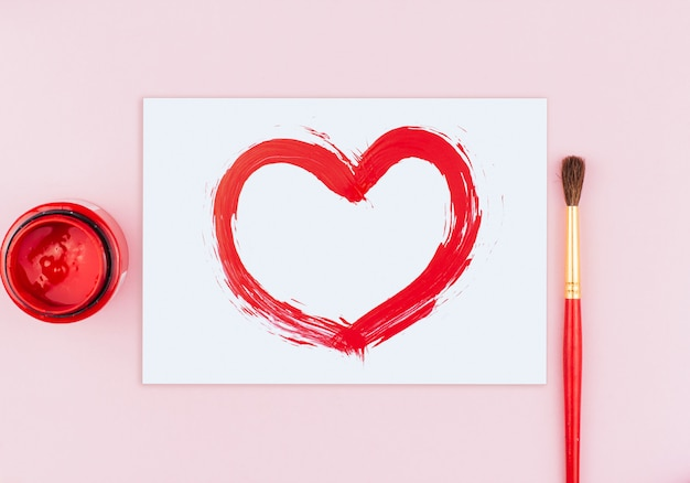 Witte kaart met een rood geverfd hart, een pot rode verf en een penseel op een roze achtergrond kopie ruimte
