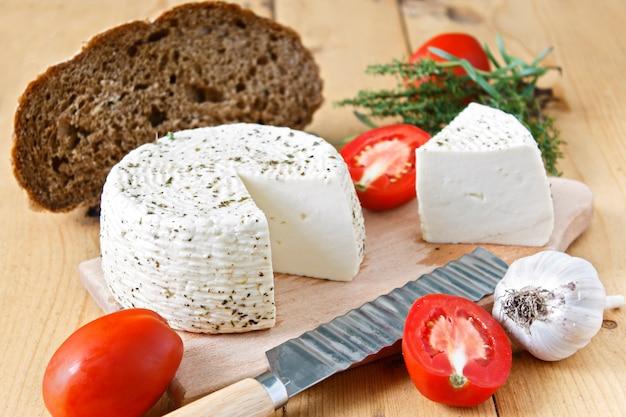 Witte kaas, brood, tomaten en knoflook op een houten achtergrond