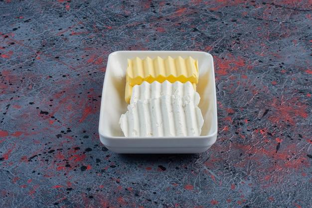 Witte kaas en boterplakken in een witte plaat.