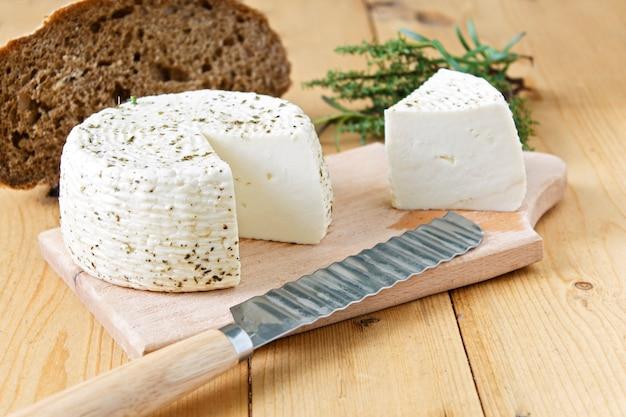Witte kaas en brood op een houten achtergrond en greens