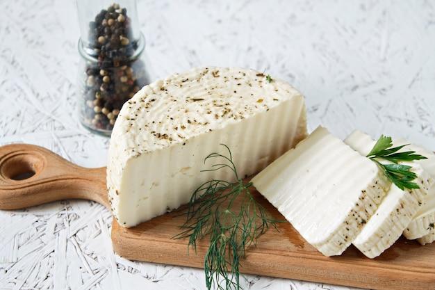 Witte kaas en kruiden op een houten bord op een witte achtergrond