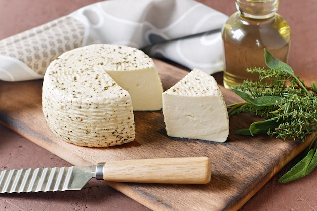 Witte kaas op een houten bord met olijfolie op een bruine achtergrond