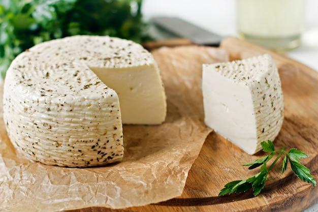 Witte kaas op een houten bord op een witte achtergrond met greens