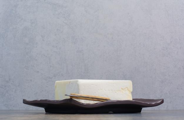 Witte kaas op zwarte plaat met mes