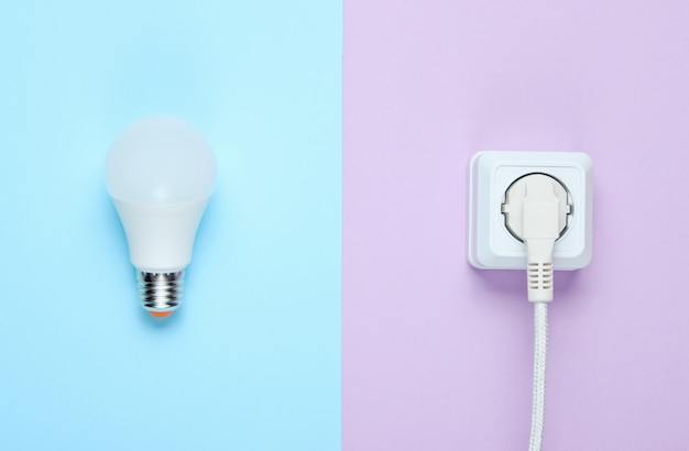 Witte kabel aangesloten op stopcontact en led-lamp. bovenaanzicht