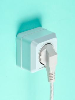 Witte kabel aangesloten op stopcontact op blauwe muur