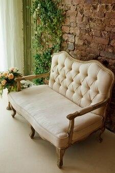 Witte kamer met roze bank, bloemen bij raam in retro woonkamer
