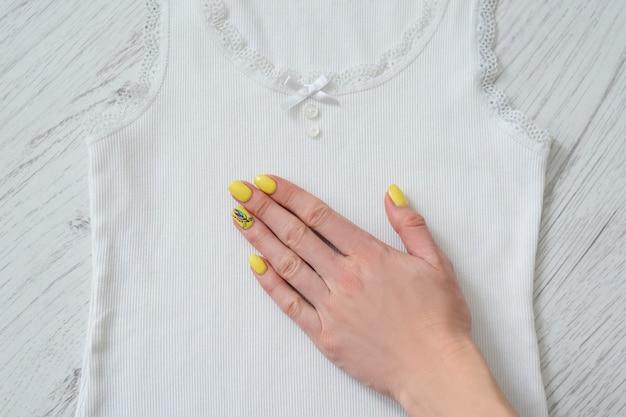 Witte kanten tanktop en vrouwelijke hand. details, close-up. modieus concept