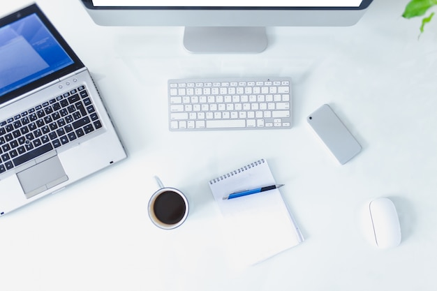 Witte kantoorruimte. laptop op tafel met kantoormateriaal.