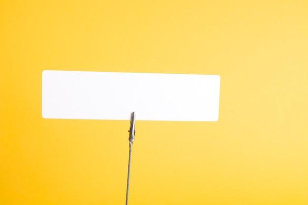 Witte kartonnen rechthoek op een wasknijper