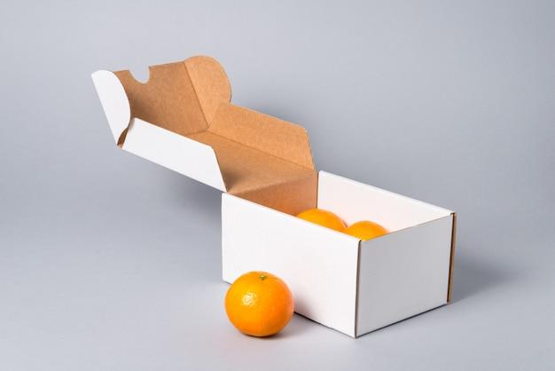Witte kartonnen taart doos met deksel met fruit, op grijze achtergrond