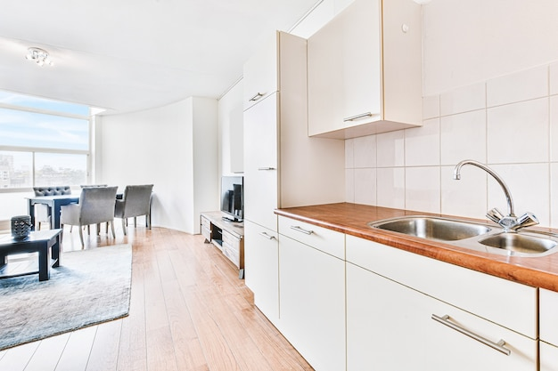 Witte kasten met houten toonbank van moderne keuken en eettafel in woonkamer van appartement