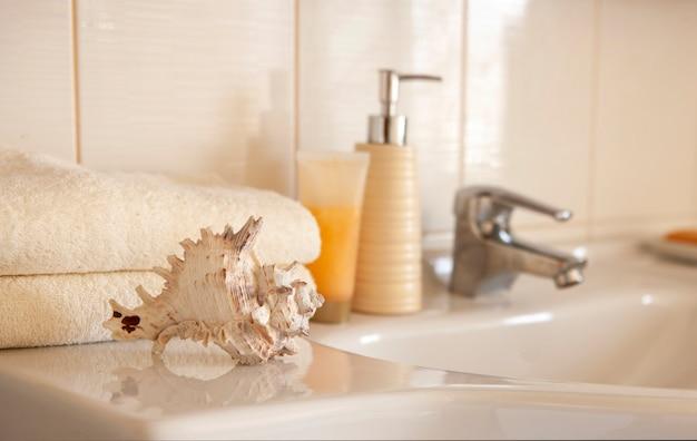 Witte katoenen badhanddoeken, keramische fles met shampoo, buis met crème en cockleshell