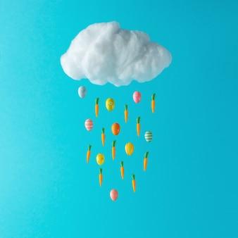 Witte katoenen wolk met paaseieren en wortelen op blauwe achtergrond