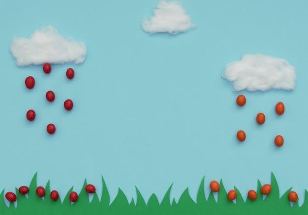 Witte katoenen wolken met regen van kleine rode en oranje paaseieren die op groen gras op blauw vallen