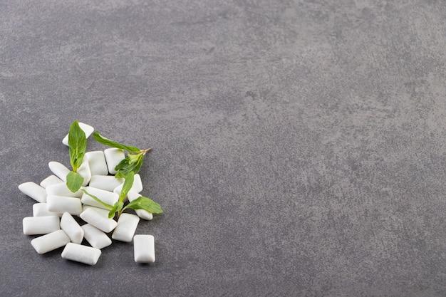 Witte kauwgom met muntblaadjes op een stenen tafel.
