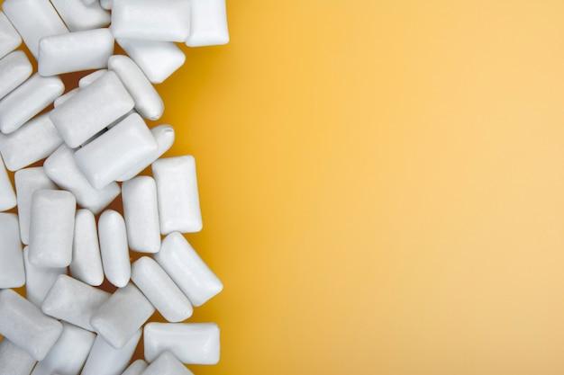 Witte kauwgom op geel met kopie ruimtetekst. plat leggen.