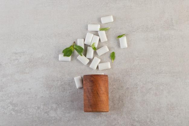 Witte kauwgom uit de container op een stenen tafel.