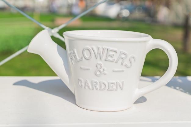 Witte keramiek bloempot in de vorm van gieter op de plank buitenshuis, tuin of interieurdecoratie.