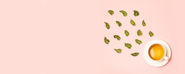 Witte keramische beker met kruiden groene of zwarte thee met muntblaadjes op roze