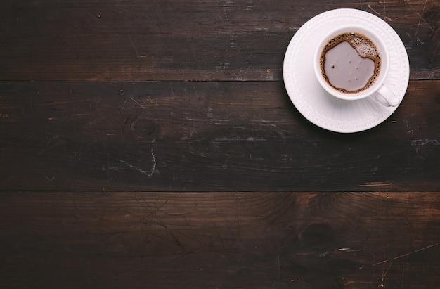 Witte keramische beker met zwarte koffie op bruine houten tafel, bovenaanzicht, kopie ruimte
