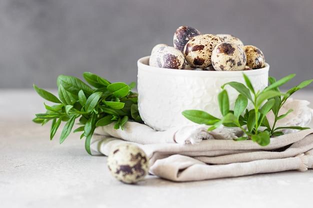 Witte keramische kom met biologische kwarteleitjes op linnen servet en groene bladeren