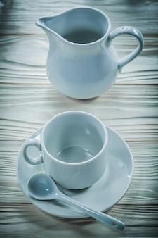 Witte keramische kop schotel theelepel creamer op houten bord