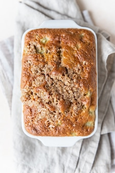 Witte keramische ovenschaal met gezonde vegan crumble cake lichte achtergrond gezond dessert