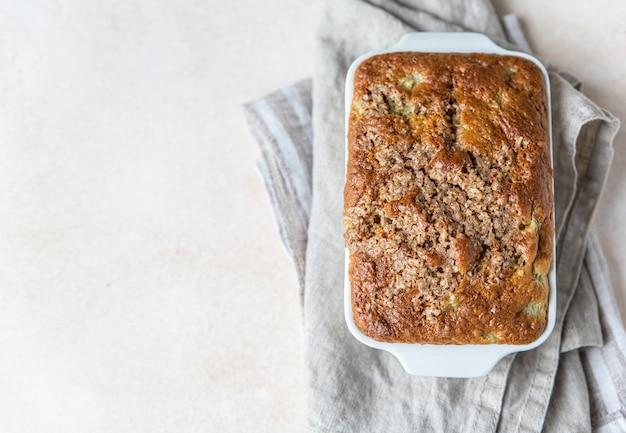 Witte keramische ovenschaal met gezonde veganistische kruimeltaart licht betonnen oppervlak gezond dessert