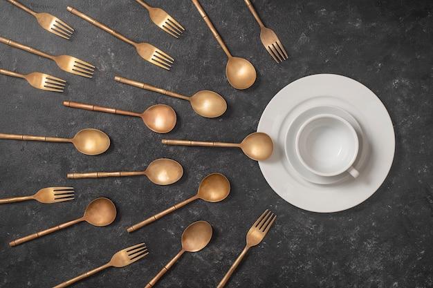 Witte keramische plaat, beker en koperen vorken en lepels zien eruit als spermacompetitie.