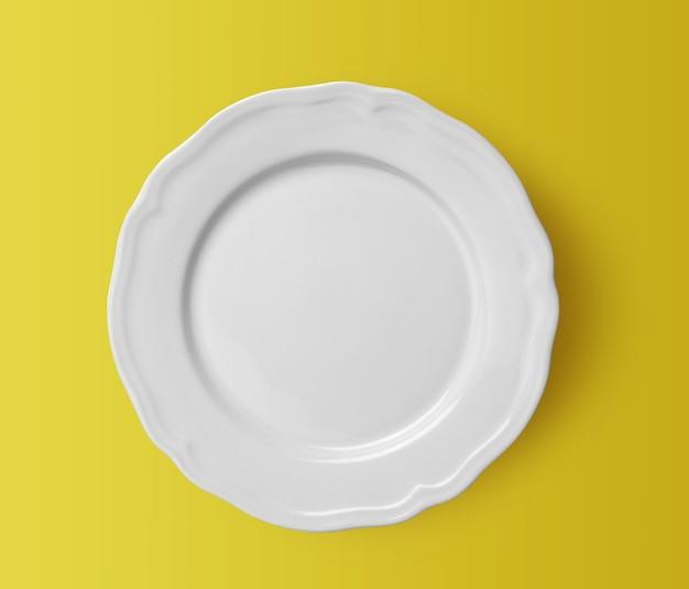 Witte keramische plaat op gele achtergrond. bovenaanzicht