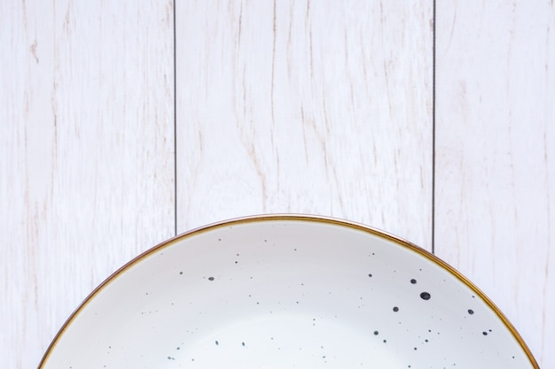 Witte keramische plaat op houten oppervlak, bovenaanzicht