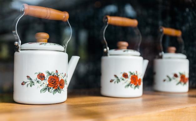 Witte keramische theepotten met houten handvat, beschilderd met rode rozen en weergegeven op een houten plank.