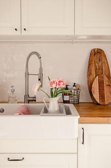 Witte keramische wasbak met kraanslang en roze ranonkelbloemen erin in een modern appartement in scandinavische stijl. gezellig huisdecoratieconcept. houten aanrechtblad met divers keukengerei.