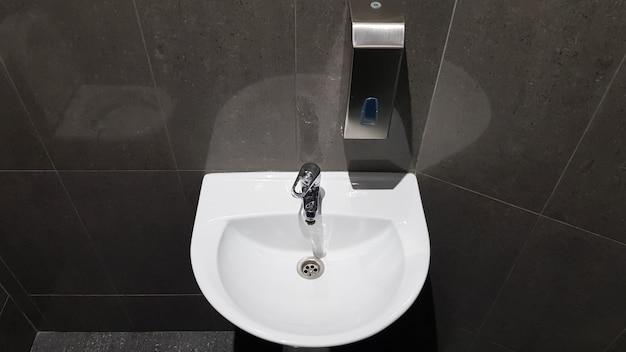 Witte keramische wastafel met chromen kraan in het toilet met grijze tegel.