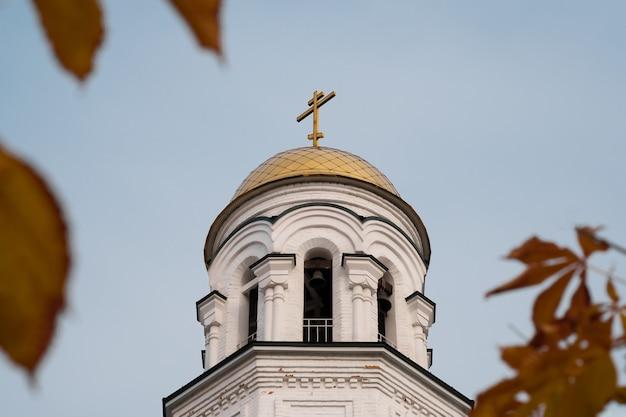 Witte kerk met herfstbladeren in defocus Premium Foto