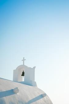 Witte kerk tegen blauwe hemel in santorini-eiland, oia, griekenland