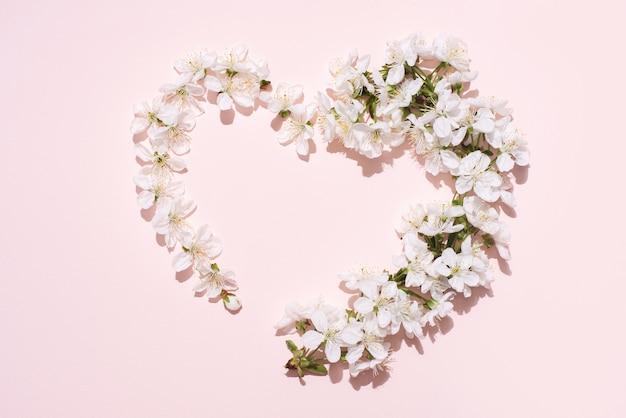 Witte kersenbloemen in de vorm van een hart op een roze