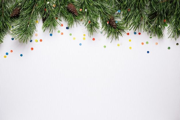 Witte kerst- en nieuwjaarsachtergrond met pijnboomtakken en feestelijke confetti